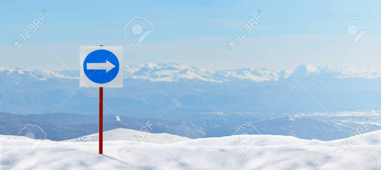 137335788-signpost-arrow-pointing-right-mandatory-direction-for-skiers-pinned-to-the-snow-snowy-peaks-in-backg